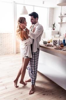 Głęboko zakochany. ciemnowłosy brodaty mężczyzna w białej koszuli, czule patrząc na żonę