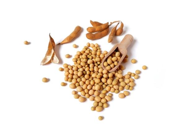 Glicyna max. suche strąki, fasola sojowa, drewniana miarka na białym tle na białym tle.