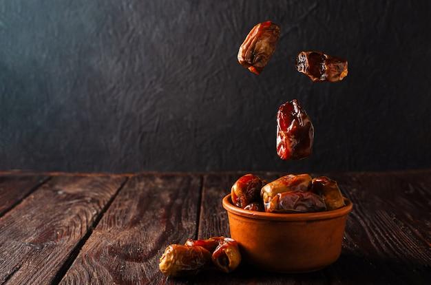 Gliniana brązowa miska z suszonymi datami na drewnianym stole. zdrowe słodycze, zdrowe odżywianie. tradycyjny deser w ramadanie.