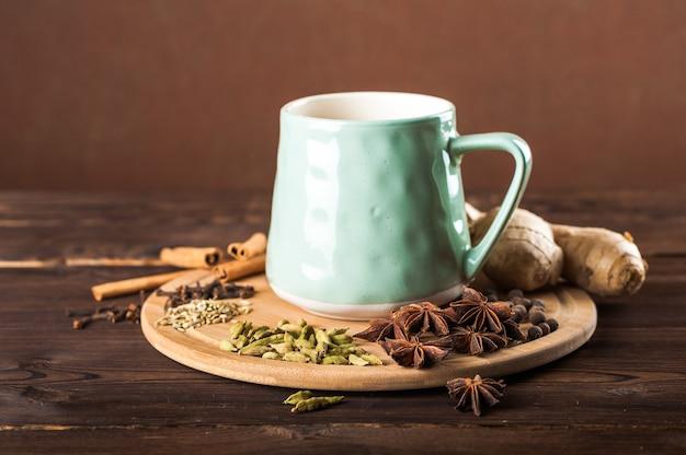 Gliniana filiżanka na drewnianej desce na ciemnym tle. filiżanka herbaty masala. przyprawy goździki, koper włoski, cynamon, kardamon, mleko.