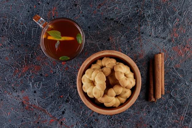 Gliniana miska babeczek z otworem i szklana filiżanka gorącej herbaty