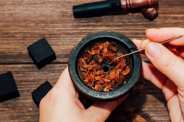 Gliniana miska do fajki wodnej z węglem kokosowym, drewniane ustniki na drewnianym tle widok z góry. dziewczyna wypełnia palenie tytoniu.