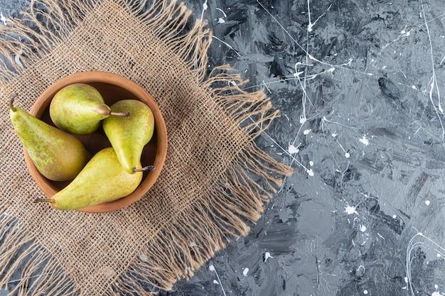 Gliniana miska dojrzałych zielonych gruszek na tle marmuru.
