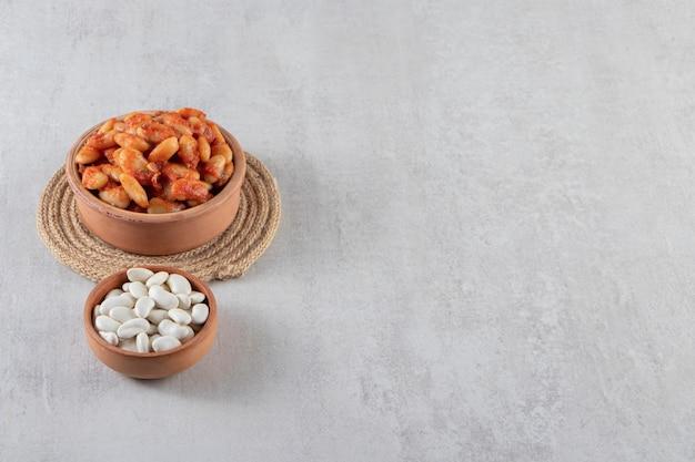 Gliniana miska gotowanej soi i surowej fasoli na kamiennym tle.
