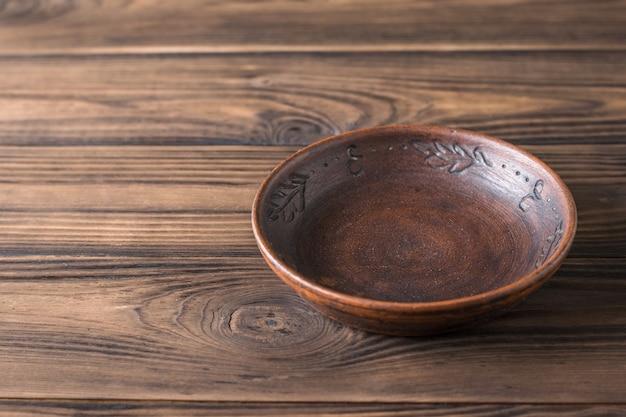Gliniana miska na brązowym drewnianym stole.