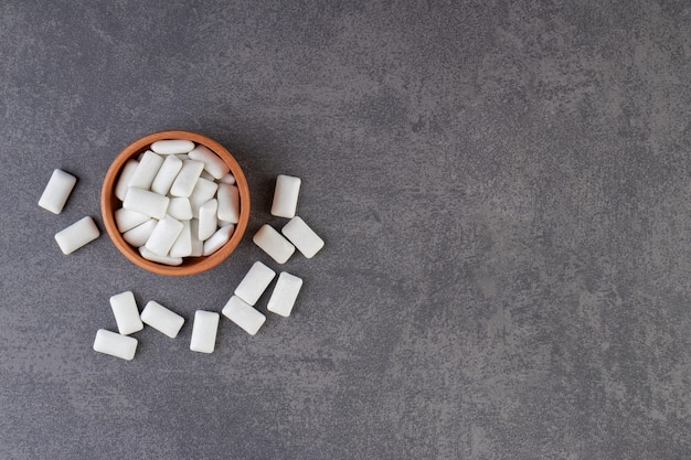 Gliniana miska pełna białych gum do żucia umieszczona na kamiennym stole.