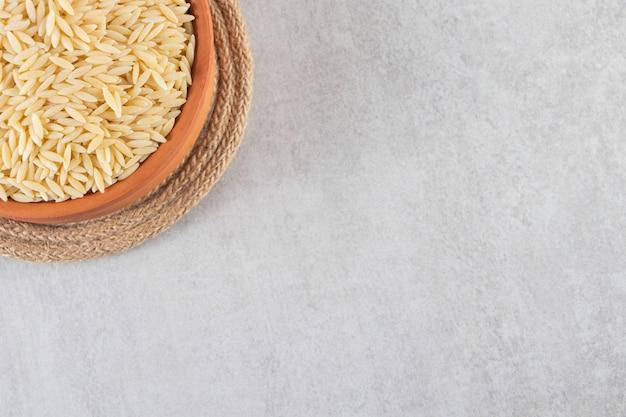 Gliniana miska pełna surowego ryżu umieszczona na kamiennym stole.