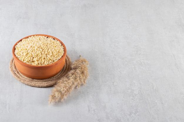 Gliniana miska pełna surowego ryżu umieszczona na kamiennym tle.
