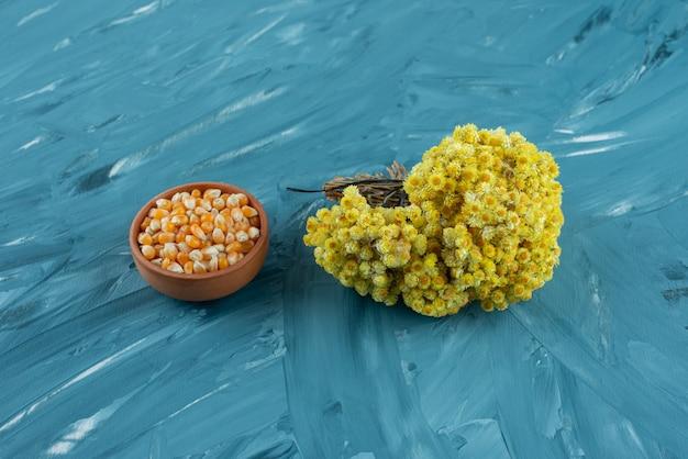 Gliniana miska surowych ziaren kukurydzy na niebieskiej powierzchni.