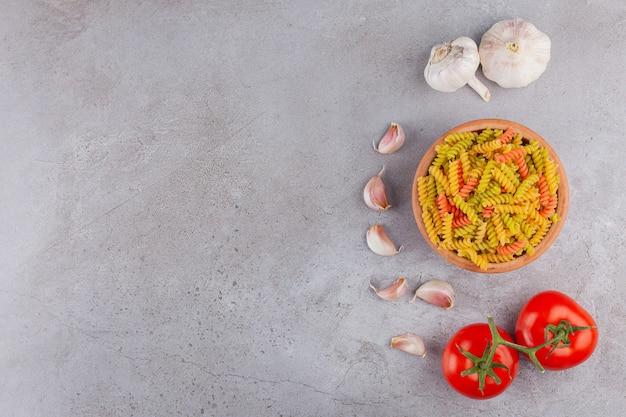 Gliniana miska wielobarwnego surowego makaronu spirali z czosnkiem i świeżymi czerwonymi pomidorami.