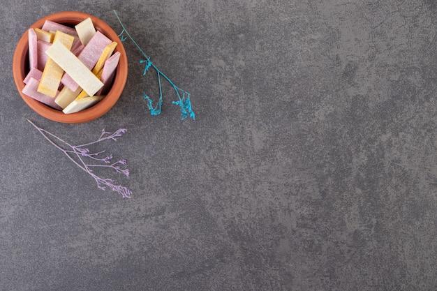 Gliniana miska z długimi paluszkami do żucia na kamiennym stole.