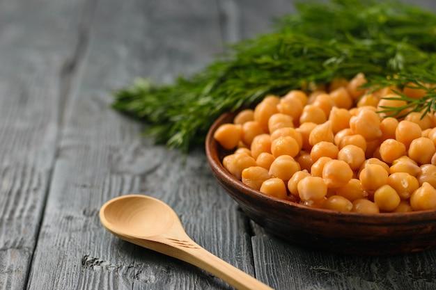 Gliniana miska z gotowaną ciecierzycą i ziołami na czarnym drewnianym stole. kuchnia wegetariańska z roślin strączkowych.