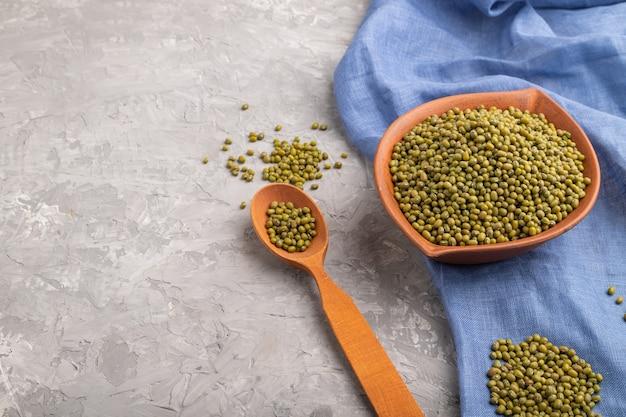 Gliniana miska z surową zieloną fasolą mung i drewnianą łyżką na szarej betonowej powierzchni i niebieskim materiale