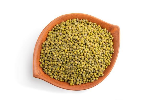 Gliniana miska z surowej zielonej fasoli mung na białym tle