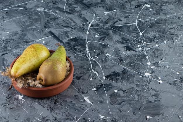 Gliniana miska ze świeżymi dojrzałymi gruszkami na powierzchni marmuru