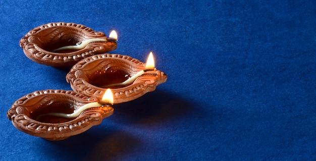 Gliniane lampy diya zapalone podczas obchodów diwali. projekt karty z pozdrowieniami indian hindu light festival o nazwie diwali