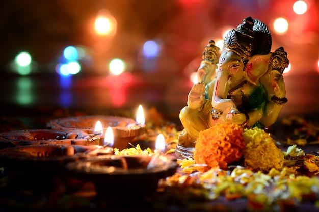 Gliniane lampy diya zapalone wraz z lordem ganesha podczas diwali celebration. greetings card design indian hindu light festival o nazwie diwali