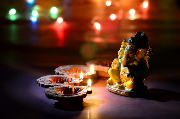 Gliniane lampy diya zapalone wraz z lordem ganesha podczas diwali celebration. projekt karty z pozdrowieniami indian hindu light festival o nazwie diwali