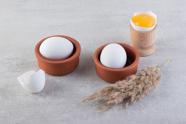 Gliniane miski białych surowych jaj z żółtkiem na kamiennym stole.