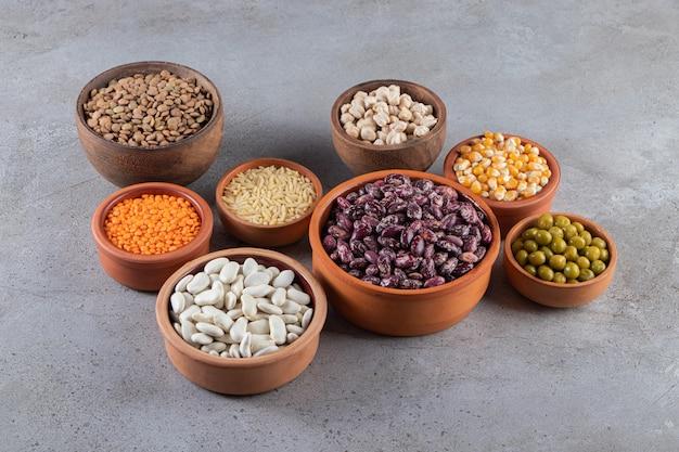 Gliniane miski pełne surowej soczewicy, grochu i fasoli na kamiennym tle.