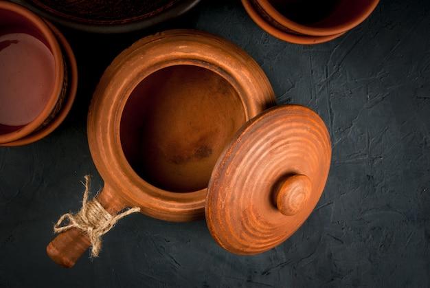 Gliniane rustykalne naczynia na kamiennym stole