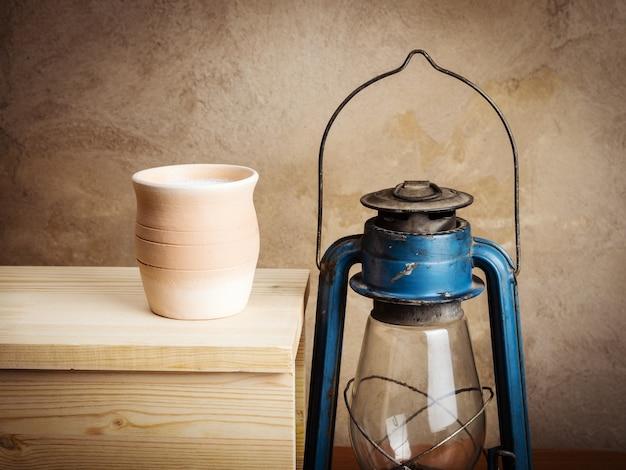 Gliniany garnek z mlekiem i latarnią naftową. martwa natura w stylu rustykalnym