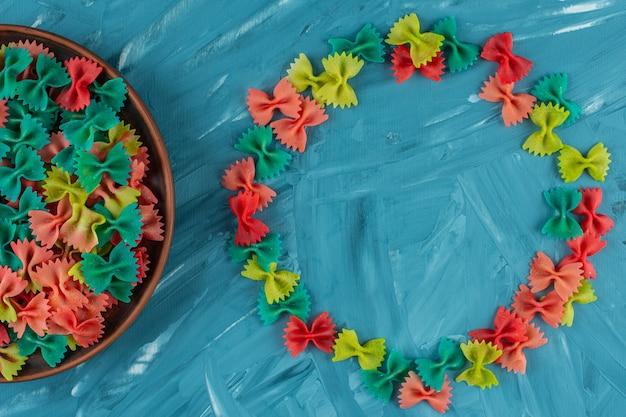 Gliniany talerz kolorowy surowego makaronu farfalle na niebieskim tle.