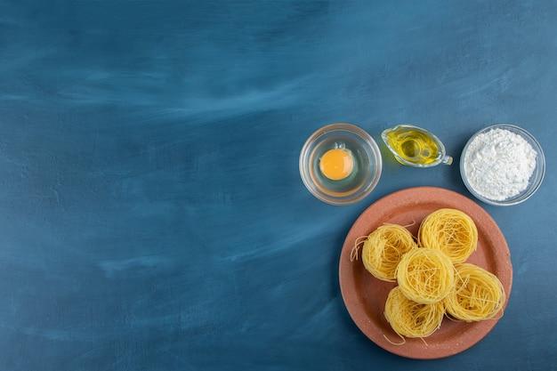 Gliniany talerz surowego suchego makaronu gniazdowego z surowym jajkiem i oliwą na ciemnoniebieskim tle.