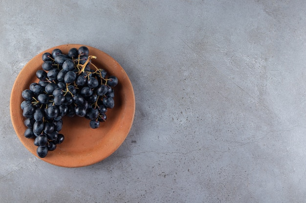 Gliniany talerz świeżych czarnych winogron na kamiennym tle.