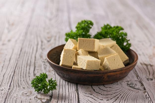 Gliniany talerz z tofu i liśćmi kędzierzawej pietruszki na drewnianym stole. produkt wegetariański.