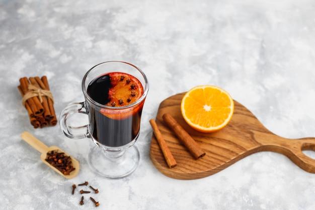 Glintwine z grzanego wina podawana w szklankach na świąteczny stół z pomarańczą i przyprawami
