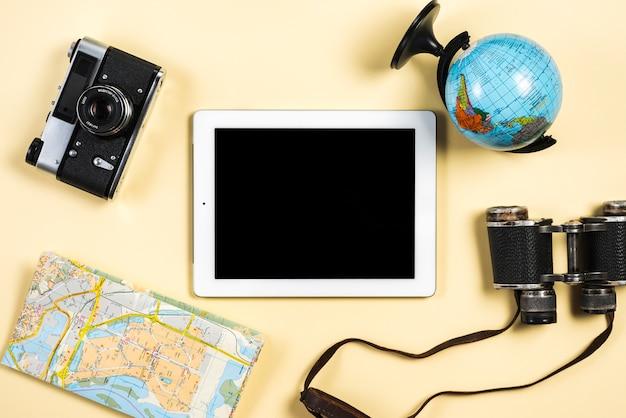 Glob; aparat fotograficzny; mapa; dwuokularowy i cyfrowy tablet na beżowym tle