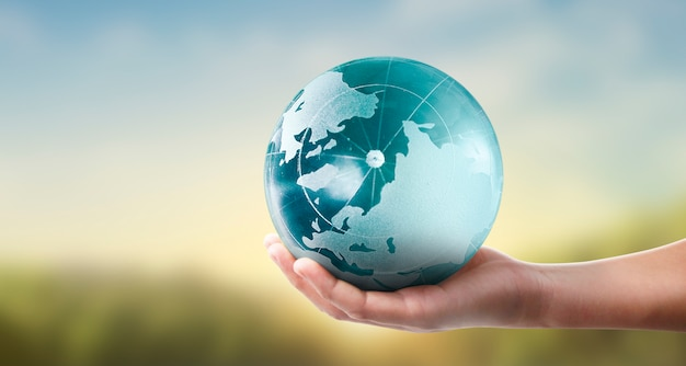 Glob, ziemia w ludzkiej dłoni, trzymająca świecącą planetę