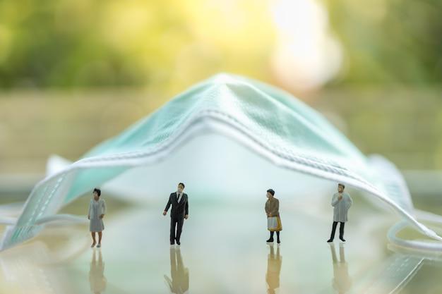Globalna opieka zdrowotna, koronawirus, ochrona i dystans społeczny. lekarz, pielęgniarka, biznesmen i kobieta miniaturowe postaci osób noszących maskę stojącą pod maską chirurgiczną