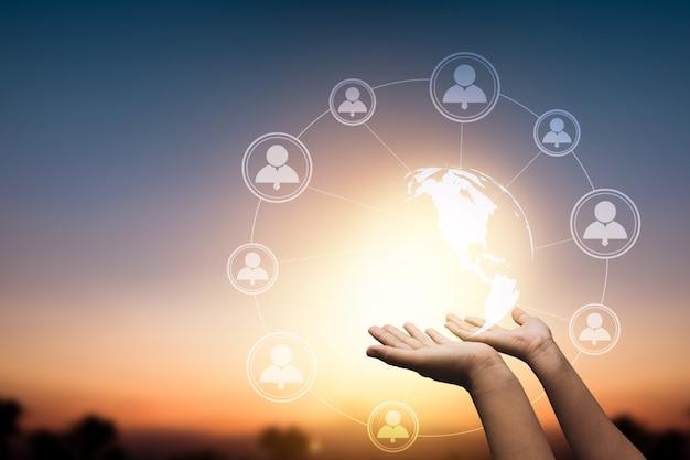 Globalna sieć społecznościowa i połączenie internetowe na abstrakcyjnych danych na całym świecie koncepcja cyberprzestrzeni, zbliżenie ręki trzymającej sieć bezprzewodową ziemia łącz się z ludźmi przez linię technologiczną 5g online o zachodzie słońca