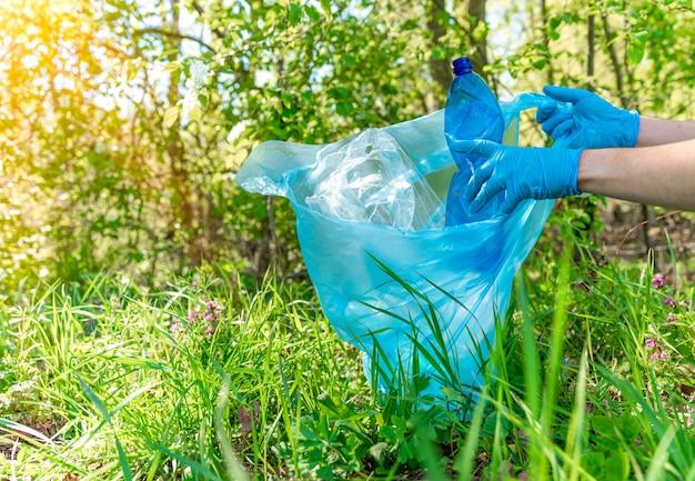 Globalne zanieczyszczenie planety odpadami z tworzyw sztucznych. wolontariusze pomagają ekologii, usuwając lasy i łąki, zbierając odpady