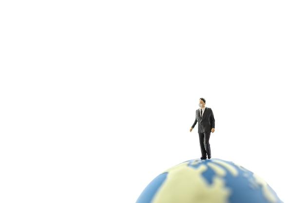 Globalny biznes i koncepcja ochrony covid-19. biznesmen miniaturowa postać ludzi noszących maskę chodzenie na mini piłka świata na białym tle z miejsca kopiowania.