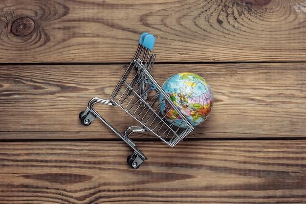 Globalny supermarket, wysyłka. wózek na zakupy z kulą ziemską na drewnianym stole