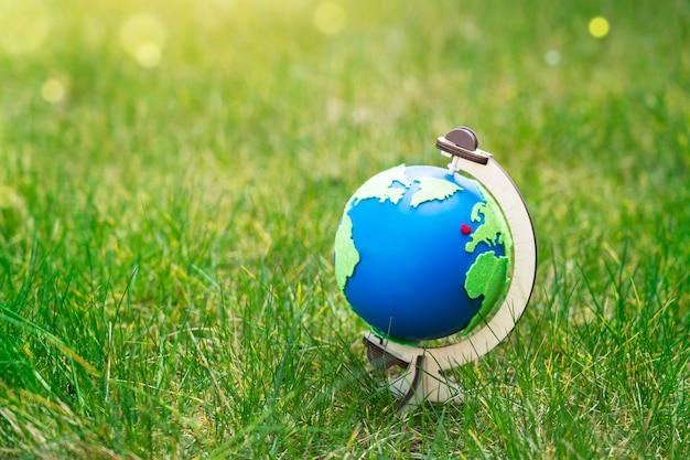 Globus planety ziemia stojący na zielonej trawie w słoneczny dzień na wiosnę lub lato, symbol eco, czerwone serce i zielona mapa na niebieskim świecie na trawniku w ogrodzie