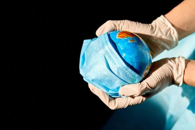 Globus w masce medycznej w rękach lekarza w ostrym świetle