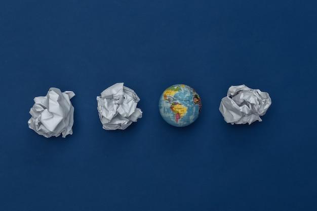 Globus z zmiętymi kulkami papieru na klasycznym niebieskim tle. koncepcja ekologiczna. kolor 2020. widok z góry