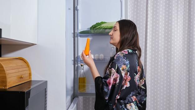 Głodna dieta młoda kobieta w ciemnej sukni z kwiatowym nadrukiem otwiera drzwi nowoczesnej lodówki, aby wziąć słodkie ciasto w kuchni w nocy zamknij widok