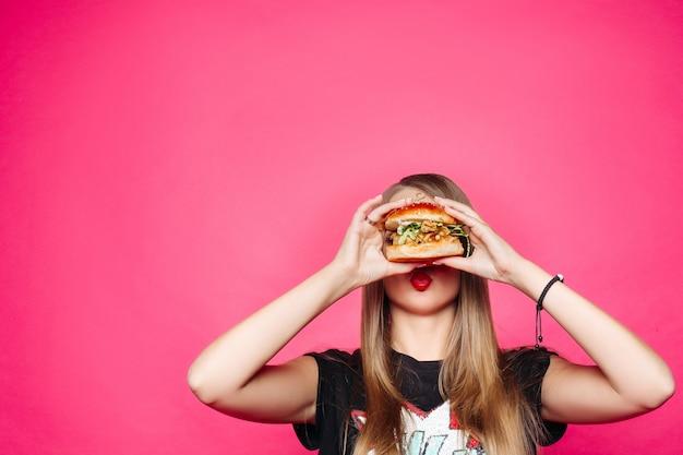 Głodna dziewczyna gryzie burgera. hamburger z kurczakiem i sałatką