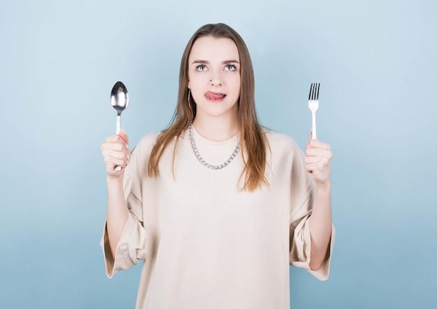 Głodna dziewczyna trzyma w dłoniach widelec i łyżkę, oblizuje usta i myśli o pysznym jedzeniu na niebieskiej ścianie