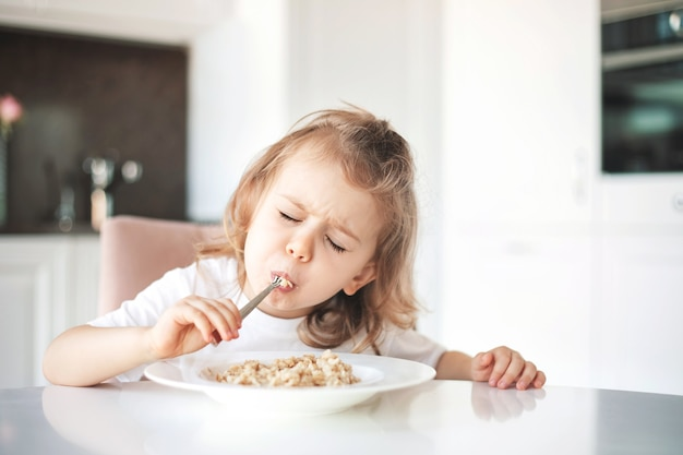 Głodna emocjonalna twarz i cieszyć się jedzeniem koncepcji. smaczne śniadanie i pyszne jedzenie. dziecko dziewczynka korzystających z miski płatków zbożowych.