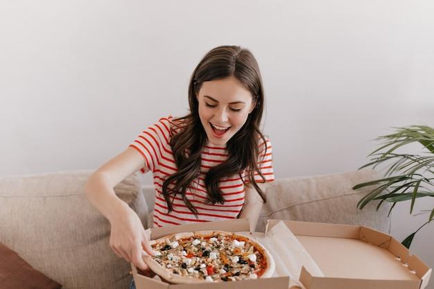 Głodna kobieta czekała na zamówienie i jest gotowa zjeść kolejną gorącą pizzę