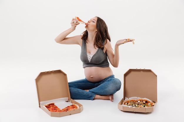 Głodna kobieta w ciąży jeść pizzę.