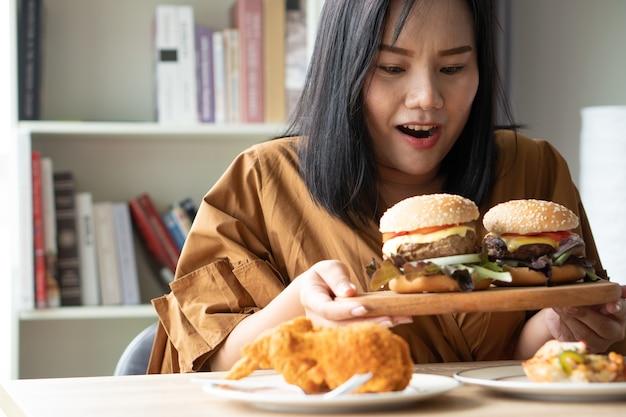 Głodna kobieta z nadwagą trzymająca hamburgera na drewnianym talerzu smażony kurczak i pizza na stole