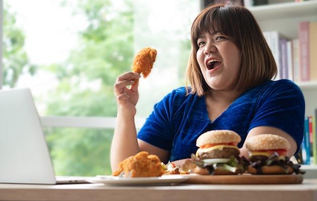 Głodna kobieta z nadwagą trzymająca hamburgera smażonego kurczaka na drewnianym talerzu i pizzę na stole