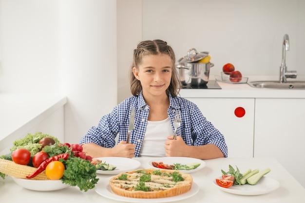 Głodna mała dziewczynka przy stole